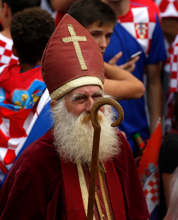 . A priest is seen in the crowds during a television broadcast of the Russia 2018 World Cup match between France and Croatia in downtown Zagreb, Croatia, Sunday, July 15, 2018. (AP Photo/Darko Vojinovic)