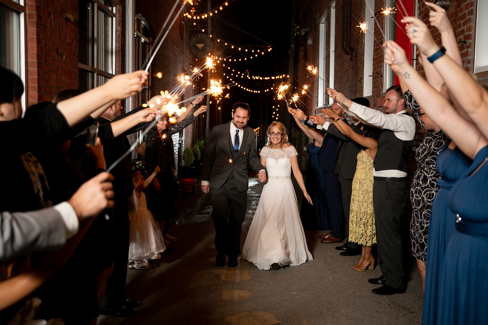 Bride and groom leaving their wedding reception as guests hold up sparklers as they walk through