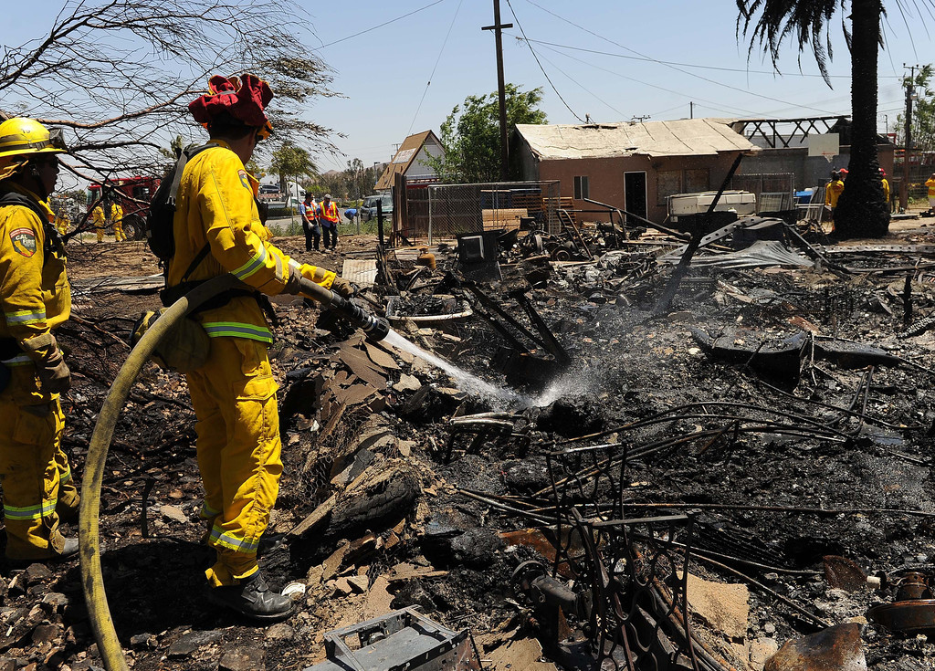 """. A vegetation fire in Jurupa Valley is 100 percent contained after destroying two homes and damaging two others. The Van Buren fire was kept to 12 acres nearly five hours after it started, said Scott Zisyak, a fire captain with Cal Fire. \""""We\'re releasing fire crews,\"""" Zisyak said about 1:30 p.m. More than 55 firefighters and sixteen fire engines responded when the fire began shortly before 8:30 a.m. No injuries were reported. In addition to the homes, five sheds and carports, 10 vehicles and one boat was destroyed by the fire.Van Buren Elementary School was evacuated and students were bussed to Mira Loma Middle School, Zisyak said. A Chevron station, located near Van Buren and Jurupa, was also evacuated.Some animals were removed from the neighborhood but residents were not asked to leave.As firefighters battled the flames, winds moved at 15 to 25 mph and stayed consistent, Zisyak said. The fire started on the center divider of Van Buren Boulevard and Jurupa Road, then jumped a road and got into nearby fields.Winds then pushed it the neighborhood. Officials believe a discarded hot object, most likely a cigarette, started the fire.LaFonzo Carter/ Staff Photographer"""