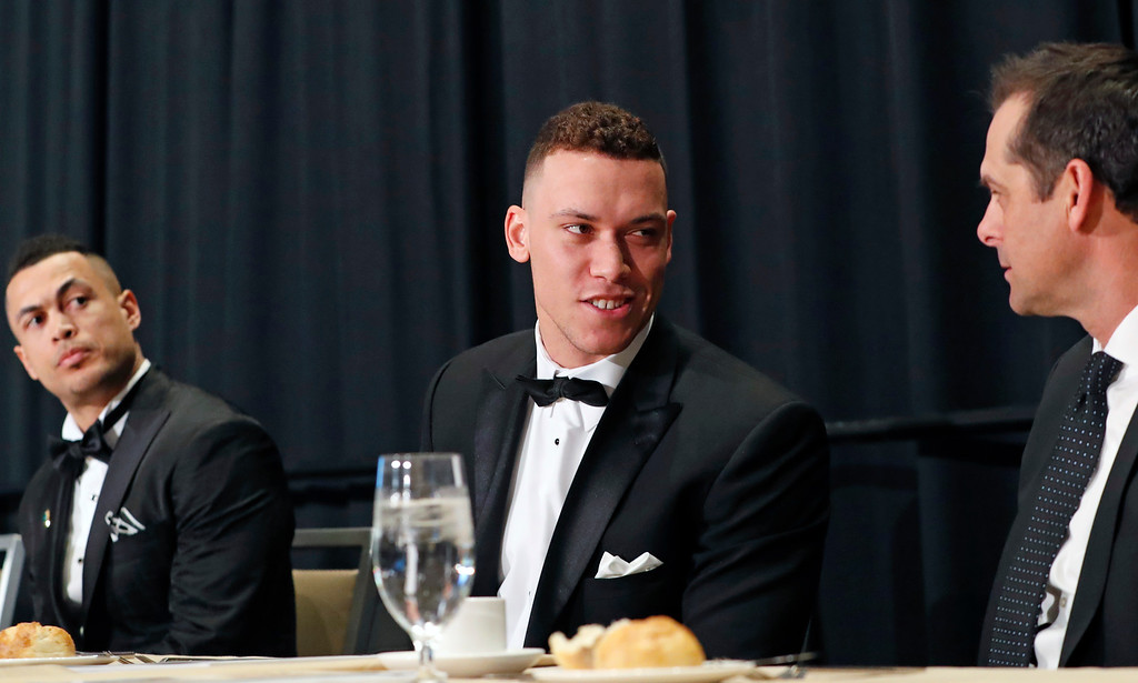 . National League Most Valuable Player Giancarlo Stanton, left, watches as American League Rookie of the Year Aaron Judge, center, talks New York Yankees manager Aaron Boone during the New York Chapter of the Baseball Writers\' Association of America annual dinner in New York, Sunday, Jan. 28, 2018. (AP Photo/Kathy Willens)