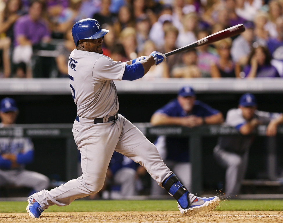 . Los Angeles Dodgers\' Juan Uribe follows through with his swing after hitting an RBI-single to drive in the go-ahead run against the Colorado Rockies in the ninth inning of the Dodgers\' 3-2 victory in a baseball game in Denver,  Thursday, July 3, 2014. (AP Photo/David Zalubowski)