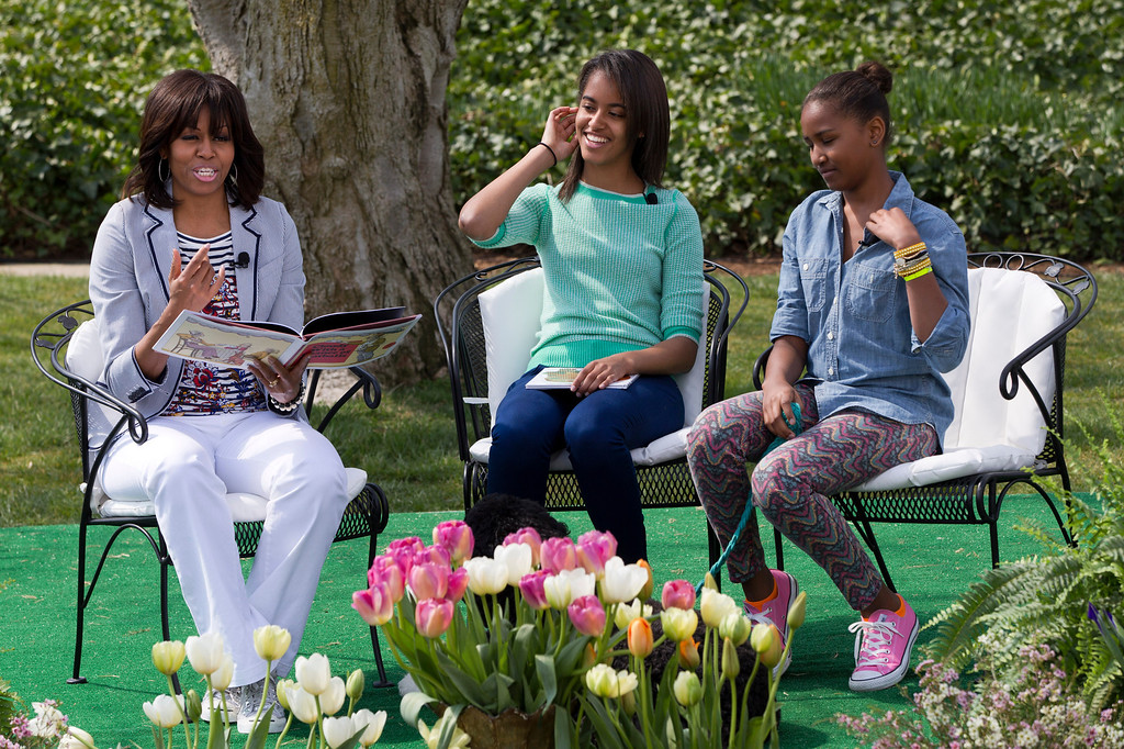 ". First lady Michelle Obama, with daughters Malia and Sasha, reads the book ""Cloudy With A Chance of Meatballs\"" to children as part of the annual White House Easter Egg Roll, Monday, April 1, 2013, on the South Lawn of the White House in Washington. (AP Photo/Jacquelyn Martin)"