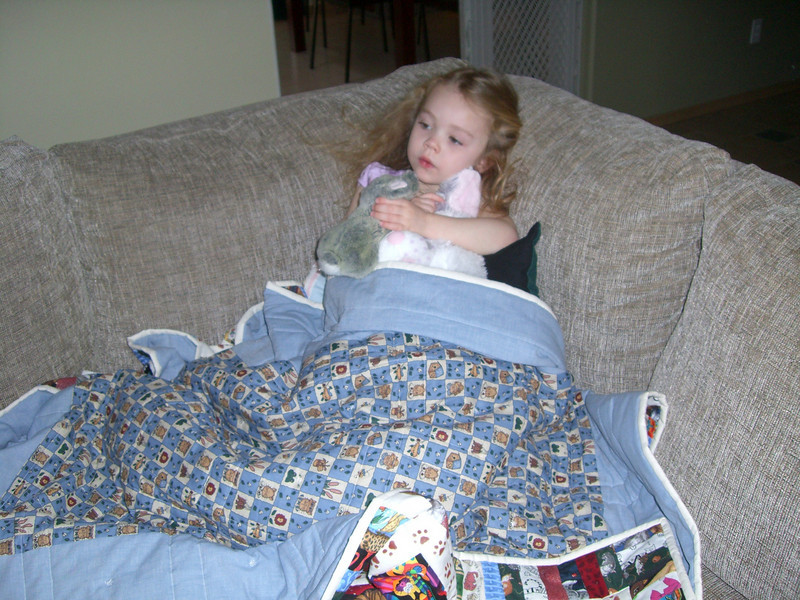 Chillin on the couch with the blanket made by Grandmama Carol.
