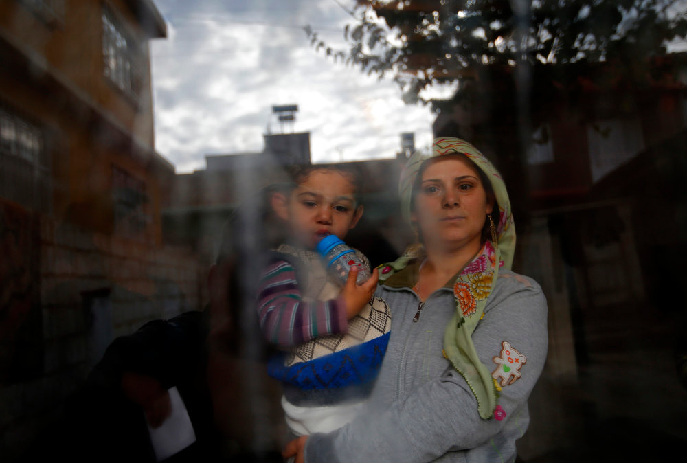 Description of . A Syrian refugee woman holds her son as she stands at the window of their friend's house at the Syrian-Turkish border town of Ceylanpinar, Sanliurfa province, December 6, 2012.     REUTERS/Laszlo Balogh