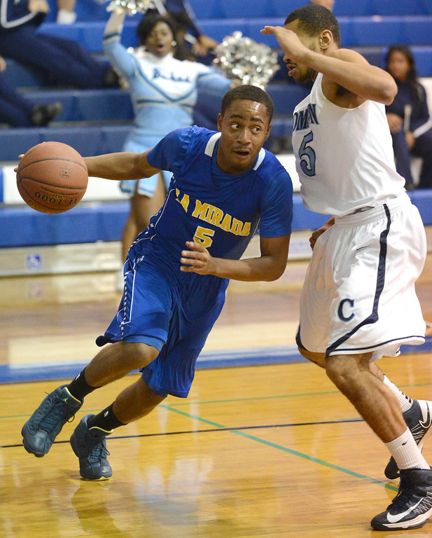 . La Mirada\'s Tyler Payne (5) drives against Compton\'s Kevlin Swint (5)in a first round CIF Division 3AAA basketball game Wednesday night in Compton. 20130213 Photo by Steve McCrank / Staff Photographer