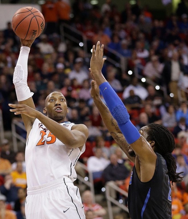 . Virginia forward Akil Mitchell (25) shoots on Memphis forward Shaq Goodwin (2) during the first half of an NCAA college basketball third-round tournament game, Sunday, March 23, 2014, in Raleigh. (AP Photo/Gerry Broome)