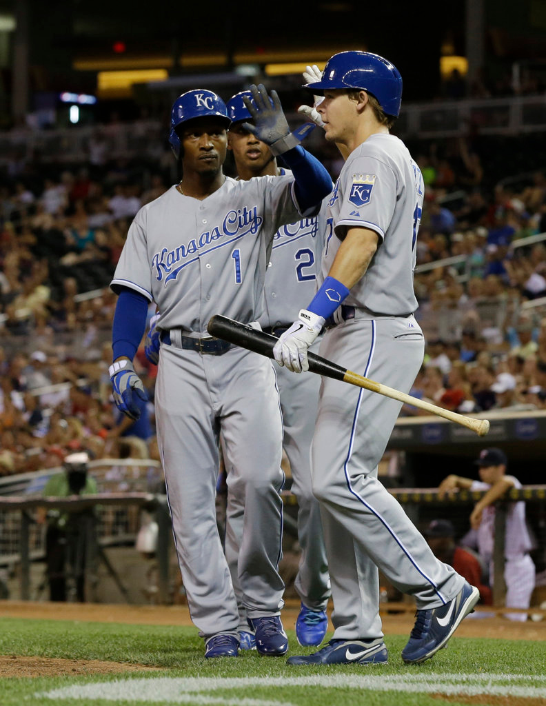 . Kansas City Royals\' Jarrod Dyson (1), Alcides Escobar (2) and Chris Getz celebrate after they scored on a bases-loaded double by Alex Gordon off Minnesota Twins pitcher Caleb Thielbar in the eighth inning of a baseball game. (AP Photo/Jim Mone)