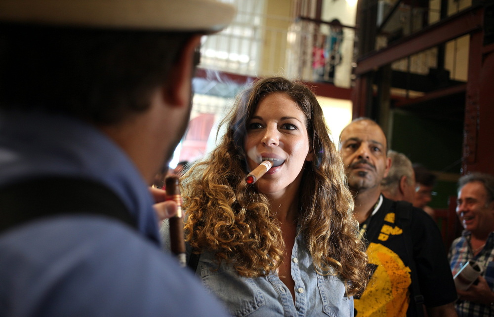 . A woman smokes a cigar at La Corona cigars factory in Havana, Cuba, 27 February 2014. Participants in the XVI Habano Festival visited the factory as part of the festival activities before it\'s final day on 28 February 2014.  (EPA/Alejandro Ernesto)