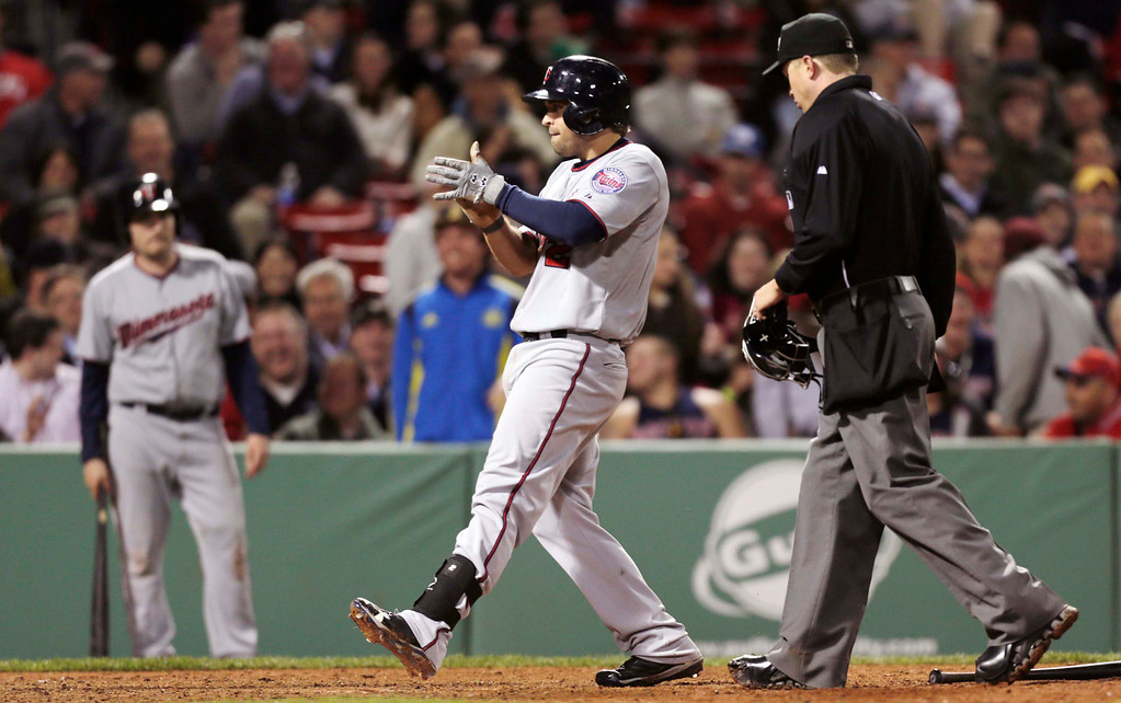 . Minnesota Twins\' Brian Dozier celebrates after crossing home plate on his solo home run during the ninth inning. (AP Photo/Charles Krupa)