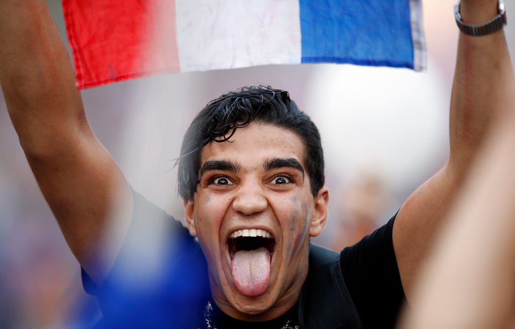 . A man holds a French flag on the Champs Elysees avenue after France won the soccer World Cup final match between France and Croatia, Sunday, July 15, 2018 in Paris. France won its second World Cup title by beating Croatia 4-2 . (AP Photo/Francois Mori)
