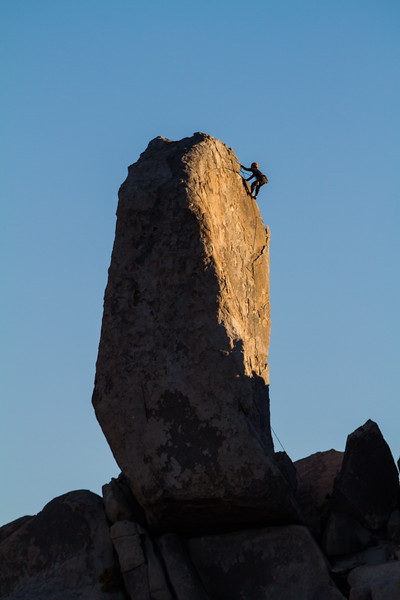 A single rock climber ascends a spire in Joshua tree national Park