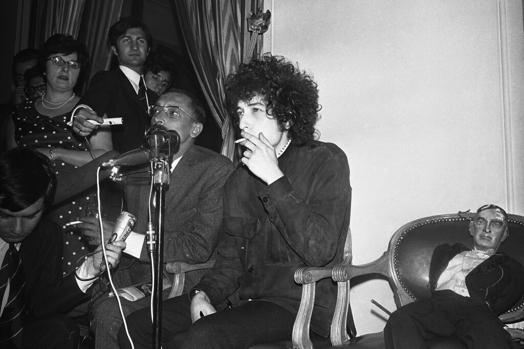 . American folk singer Bob Dylan smokes as he faces the media during a press conference at the Hotel George V in Paris, France on May 23, 1966. He will appear on Tuesday at the Paris Olympia music-hall. Beside him is a puppet. (AP Photo/Pierre Godot)