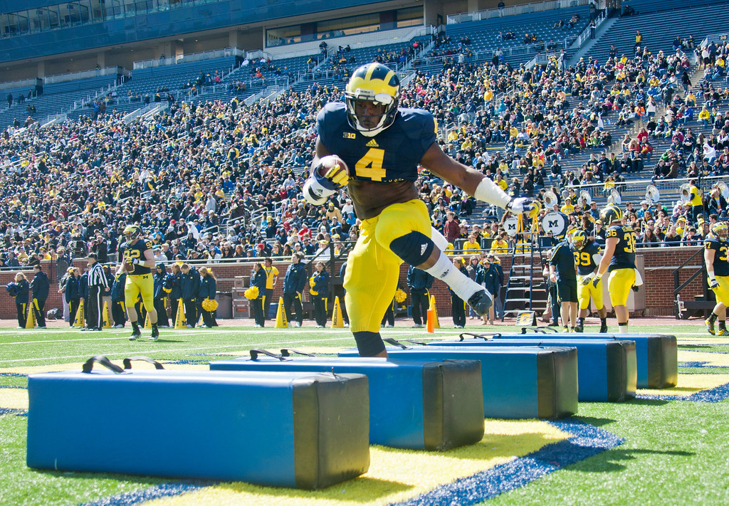 . Michigan running back De\'Veon Smith (4) steps through an obstacle drill during the football team\'s annual spring game, Saturday, April 5, 2014, in Ann Arbor, Mich. (AP Photo/Tony Ding)