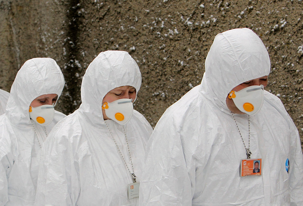 . Workers wearing protective suits and masks exit a fallout shelter during a nuclear accident simulation as part of a safety regulations exercise at Nuclear Power Plant Dukovany in Dukovany March 26, 2013.     REUTERS/David W Cerny