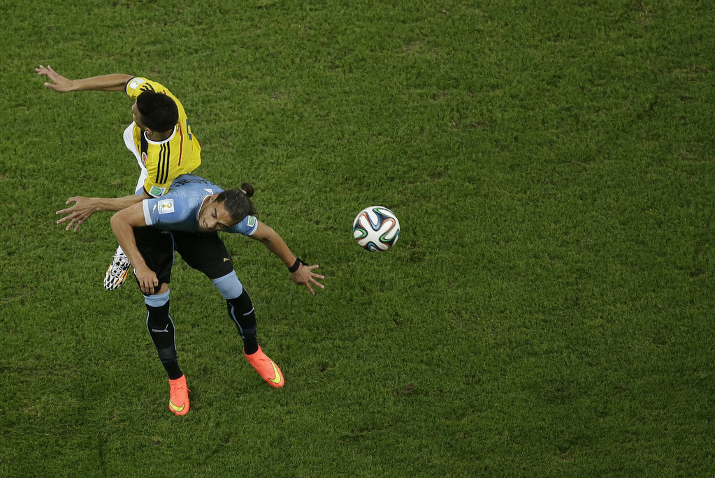 . Colombia\'s defender Cristian Zapata (TOP) challenges Uruguay\'s defender Martin Caceres for the ball during the Round of 16 football match between Colombia and Uruguay at The Maracana Stadium in Rio de Janeiro on June 28, 2014,during the 2014 FIFA World Cup.  FELIPE DANA/AFP/Getty Images