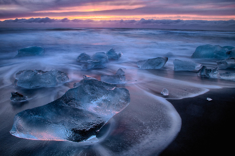 Icebergs on volcanic beach at sunset, Iceland