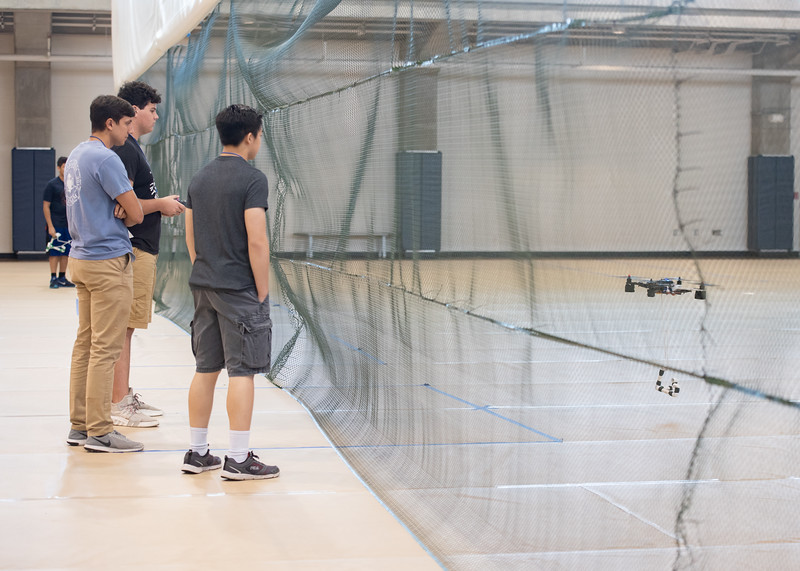 Camp mentor Peter Kline (left) watches as Ty Bamhart attempts to use a drone to pick up objects as part of the UAS Summer Institute.