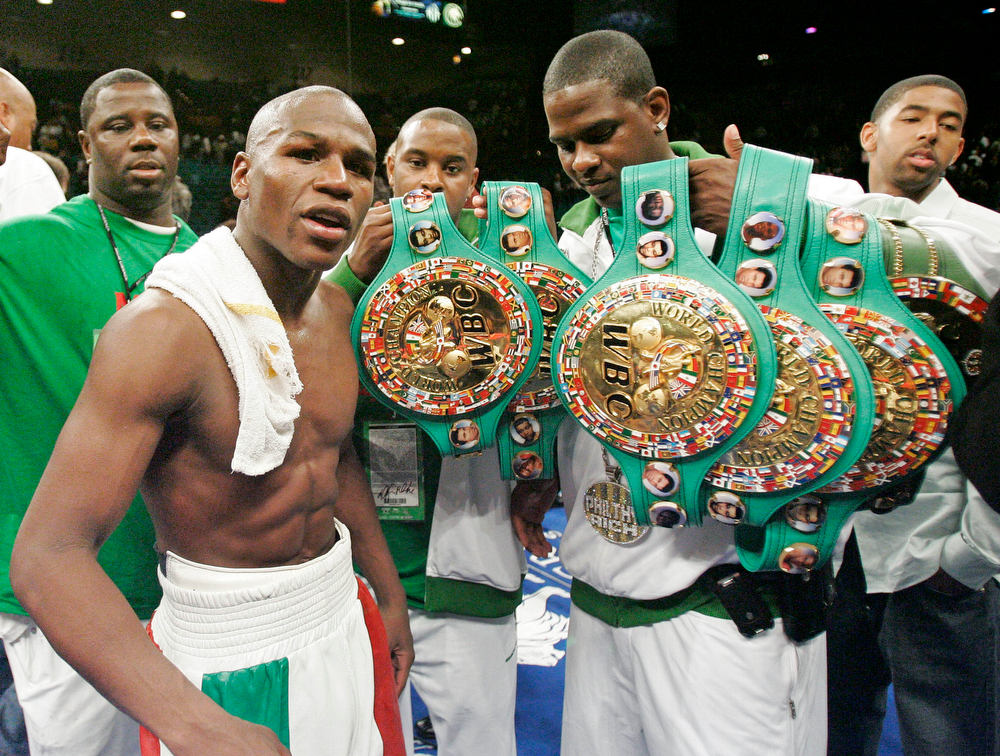 . Floyd Mayweather  Jr., foreground, poses with his six title belts after defeating Oscar De La Hoya in split decision to win the WBC super welterweight world championship bout on Saturday, May 5, 2007, at the MGM Grand Garden Arena  in Las Vegas. (AP Photo/Kevork Djansezian)
