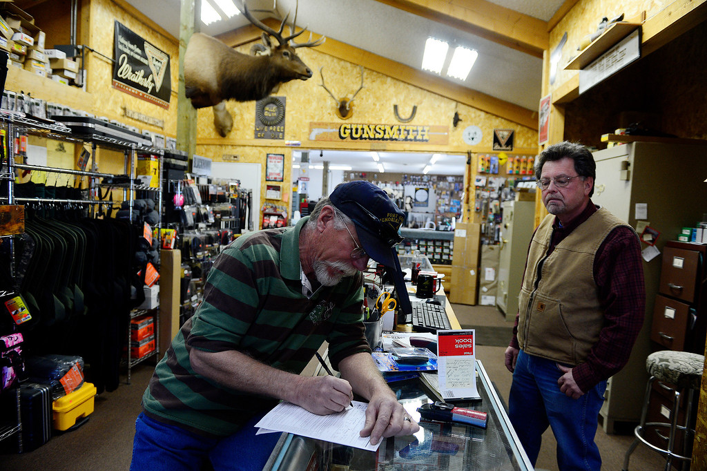 . MONTE VISTA, CO - FEBRUARY 26: Alan McFadden fills out a background check as Valley Guns owner Carlton Thomas looks on. Thomas, who knows McFadden well, said that even if his own brother came in, he\'d have to fill out the check. Gun owners in southern Colorado largely agree that responsible ownership begins at home. (Photo by AAron Ontiveroz/The Denver Post)