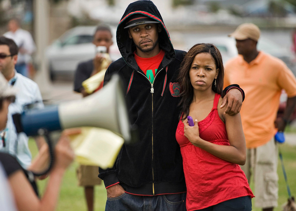 . Thomas Bouldin (L) of Jacksonsville, Florida, and Sabrina Cochran, of Smiths Station, Alabama, listen to a speaker during an open forum to discuss the George Zimmerman second-degree murder trial and verdict at Melon Park in Sanford, Florida, July 14, 2013. U.S. President Barack Obama called for calm on Sunday after the acquittal of Zimmerman in the shooting death of black teenager Trayvon Martin, as civil rights demonstrators planned rallies in a handful of cities to condemn racial profiling. REUTERS/Steve Nesius