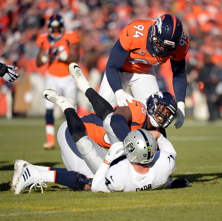 . DENVER, CO - DECEMBER 28: Von Miller (58) of the Denver Broncos sacks Derek Carr (4) of the Oakland Raiders early in the first quarter.  The Denver Broncos played the Oakland Raiders at Sports Authority Field at Mile High in Denver on December, 28 2014. (Photo by Joe Amon/The Denver Post)