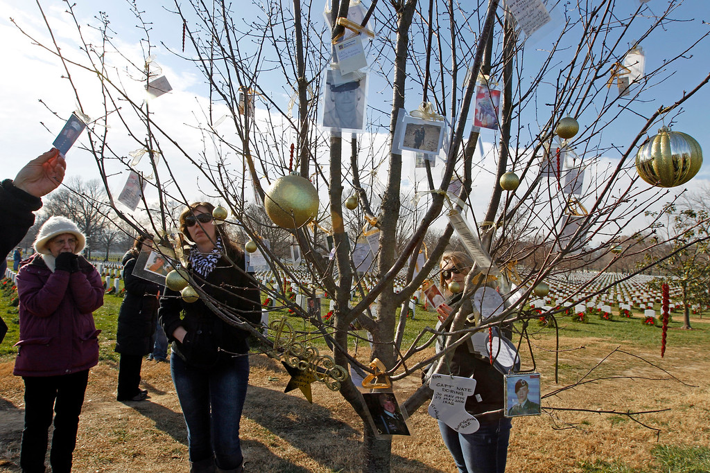 . Visitors pause to see a decorated tree with photos of fallen soldiers, as volunteers lay wreaths at each grave at Arlington National Cemetery in Arlington, Va., Saturday, Dec. 15, 2012, during Wreaths Across America Day. Wreaths Across America was started in 1992 at Arlington National Cemetery by Maine businessman Morrill Worcester and has expanded to hundreds of veterans\' cemeteries and other locations in all 50 states and beyond. (AP Photo/Jose Luis Magana)
