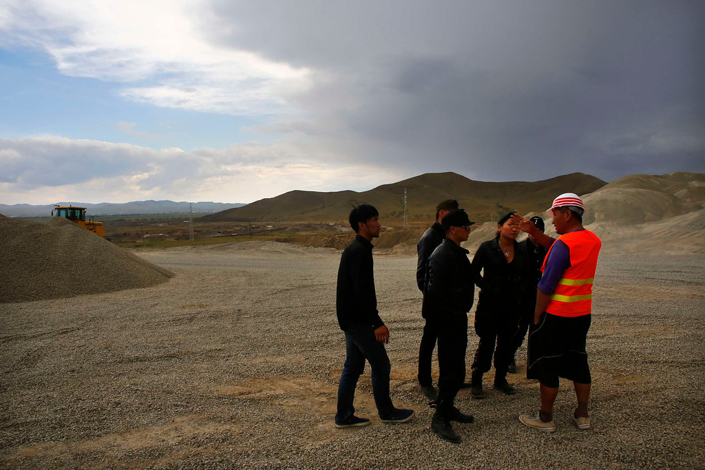 . Members of the Mongolian neo-Nazi group Tsagaan Khass talk to a worker at a quarry southwest of Ulan Bator June 23, 2013. The group has rebranded itself as an environmentalist organisation fighting pollution by foreign-owned mines, seeking legitimacy as it sends Swastika-wearing members to check mining permits.Over the past years, ultra-nationalist groups have expanded in the country and among those garnering attention is Tsagaan Khass, which has recently shifted its focus from activities such as attacks on women it accuses of consorting with foreign men to environmental issues, with the stated goal of protecting Mongolia from foreign mining interests. This ultra-nationalist group was founded in the 1990s and currently has 100-plus members. Picture taken June 23, 2013. REUTERS/Carlos Barria