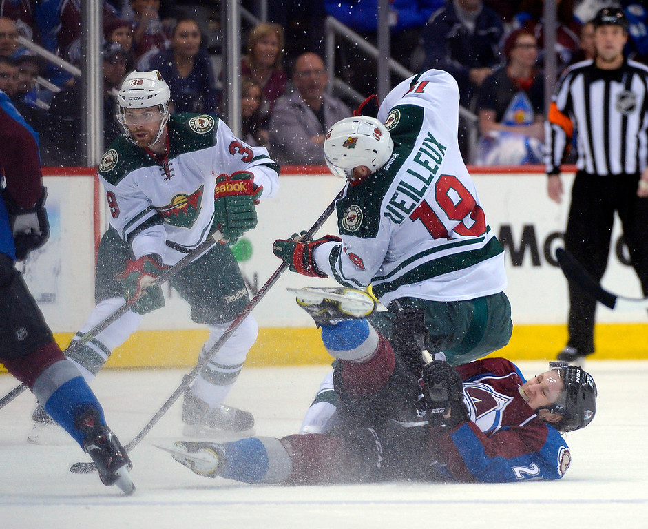 . Colorado Avalanche center Nathan MacKinnon (29) slides into and takes down Minnesota Wild center Stephane Veilleux (19) during the second period.   (Photo by John Leyba/The Denver Post)