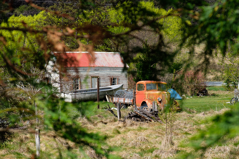 Decaying vintage car next to farmhouse in South Island, New Zealand