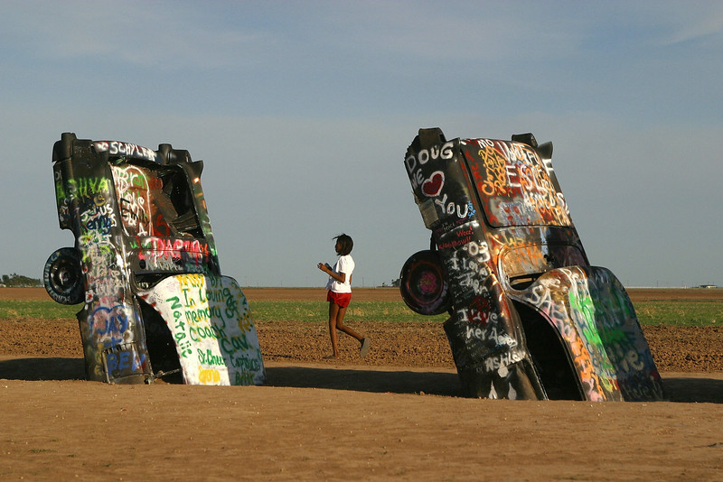 ". A visitor tours the ""Cadillac Ranch\"" on historic Route 66  in Amarillo, 06 July 2003. As a tribute to America\'s relationship with one of it\'s favorite automobiles, a collective of artists called Ant Farm  in 1974 placed 10 Cadillacs, ranging from a 1949 Club Coupe to a 1963 Sedan, in a wheat field located west of Amarillo.  Visitors are encourage to draw or paint on the cars.  Cadillac Ranch is a popular stopping off point for tourists on historic Route 66 which stretches from Chicago to Los Angeles.  (AFP PHOTO / Robyn BECK)"