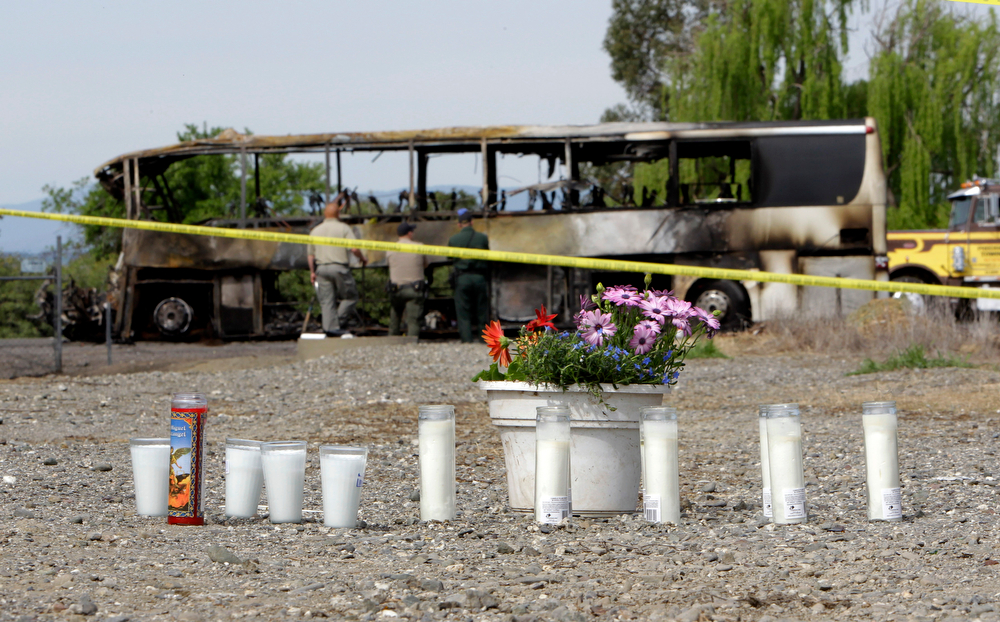 . Candles and flowers are seen at a make-shift memorial, Friday, April 11, 2014, for the victims of a multi-vehicle accident that included a tour bus and a FedEX truck crashed on Interstate 5  in Orland, Calif.  Ten people were killed and dozens injured in the fiery crash, Thursday, between the truck and a bus seen in background, carrying high school students on a visit to a Northern California College.(AP Photo/Rich Pedroncelli)