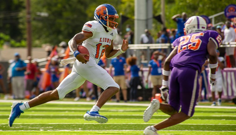 Florida Memorial University quarterback Antoine Williams runs toward daylight ahead of Edward Waters' Martavius Davis (25) during the first half of an Aug. 28, 2021 contest. (Photo by Will Brown)
