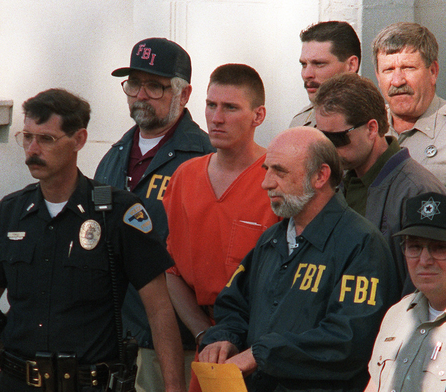 . PERRY, OK - APRIL 21:  Timothy McVeigh, 27, (C) is led 21 April 1995 from the Noble County Courthouse in Perry, Oklahoma, by FBI agents after being charged with involvement in the 19 April 1995 bombing of the Alfred P. Murrah Federal Building in Oklahoma City, Oklahoma. McVeigh was found guilty 02 June in Denver on 11 counts dealing with the bombing, including the deaths of eight federal agents. McVeigh, convicted on first-degree murder charges for the 19 April fuel-and-fertilizer bomb explosion, was sentenced to death in 1997. The blast, the worst terror attack on US soil, killed 168 people and injured more than 500.  (BOB DAEMMERICH/AFP/Getty Images)