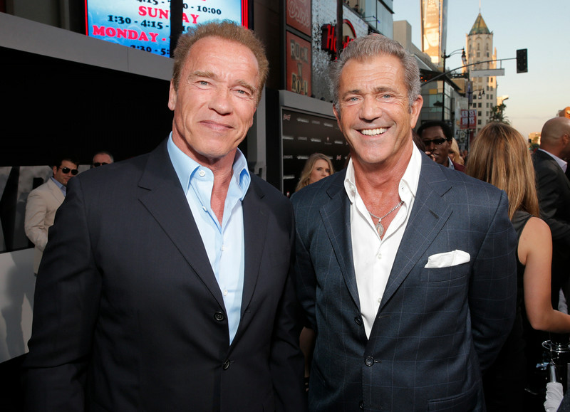 ". Arnold Schwarzenegger, left, and Mel Gibson arrive at the Los Angeles premiere of ""The Expendables 3\"" at the TCL Chinese Theatre on Monday, Aug. 11, 2014. (Photo by Todd Williamson/Invision/AP)"