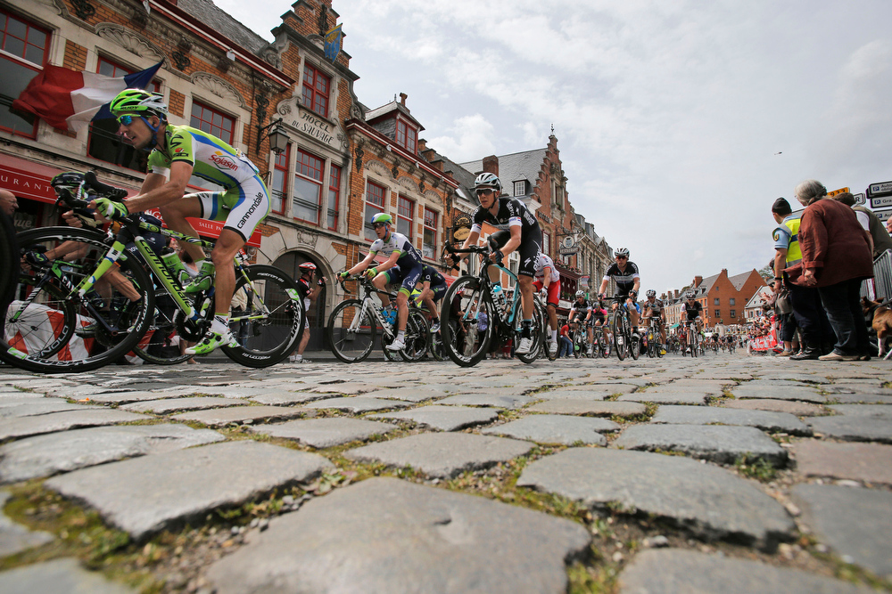Description of . The pack with France's Jean Marc Marino, far left, passes over cobblestones in Cassel, during the fourth stage of the Tour de France cycling race over 163.5 kilometers (101.6 miles) with start in Le Touquet and finish in Lille, France, Tuesday, July 8, 2014. (AP Photo/Christophe Ena)