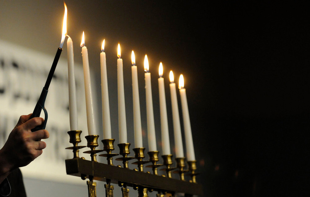 Description of . The last candle is lit during the service for Yom HaShoah, a Holocaust Day of Remembrance, at the Holocaust Memorial Center in Farmington Hills, Mich., on Sunday, April 7, 2013.  (AP Photo/Detroit News, Elizabeth Conley)