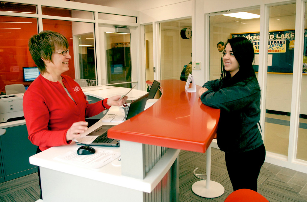 . Susan Kokish, left, helps fellow student Hayley Foti open up an account at the student-run branch of the Cardinal Community Credit Union at Lakeland Community College in January 2014. (News-Herald file)