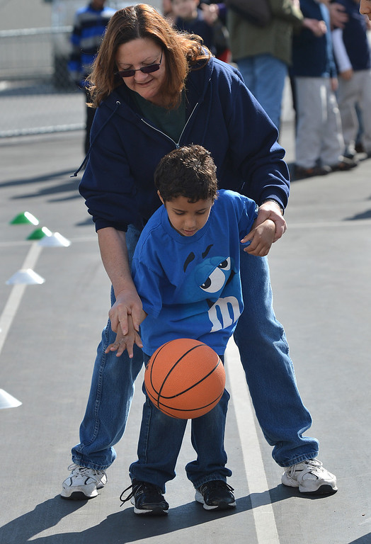. Pam Ward, an instructional assistant for the Contra Costa County Office of Education\'s East County Student Programs, helps teach Malik, 6, of Antioch how to dribble the basketball during a Special Olympics basketball skills event at Turner Elementary School in Antioch, Calif., on Friday March 8, 2013.  (Dan Rosenstrauch/Staff)