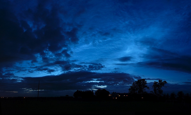 Stunning noctilucent display from 14 July 2009 Leics, UK. This was such an intense display and so early compared to previous sightings, 10.30pm. There was lots of cloud cover too but such was the intensity of the electric blues that it made hardly any difference! Taken with Olympus E3 & 12-60mm SWD