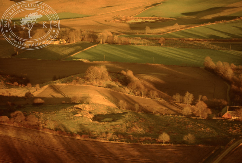 Farmland west of Ravlunda church - with plantations, buildings and prehistoric remains. Experimentally photographed with yellow filter (20 November, 1988). | LH.0268