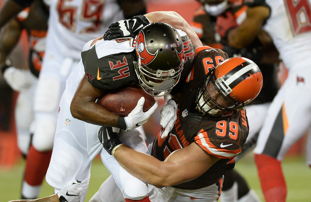 . Cleveland Browns outside linebacker Paul Kruger (99) stops Tampa Bay Buccaneers running back Charles Sims during the first quarter of an NFL football game Friday, Aug. 26, 2016, in Tampa, Fla. (AP Photo/Jason Behnken)