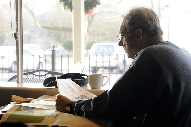 A man reads the newspaper at a table beside an enormous window at The Plaid Apron in Knoxville, TN on Monday, December 15, 2014. Copyright 2014 Jason Barnette