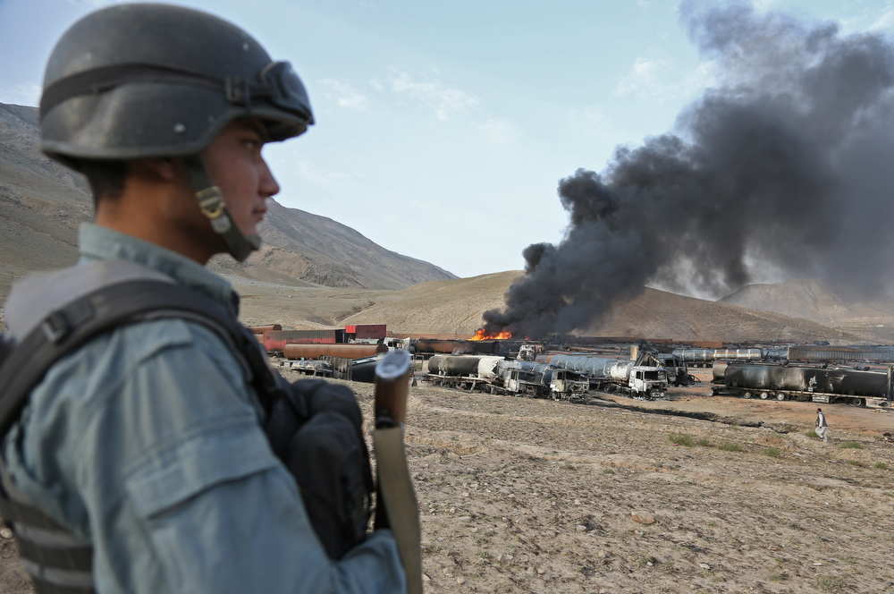 . An Afghan soldier stands guard at the site of burning oil tankers after an attack claimed by Taliban militants on the outskirts of Kabul, Afghanistan, Saturday, July 5, 2014. An Afghan security official says at least 400 fuel tankers caught fire late Friday night in a parking lot in the outskirts of Kabul and there are fears of casualties. (AP Photo/Rahmat Gul)