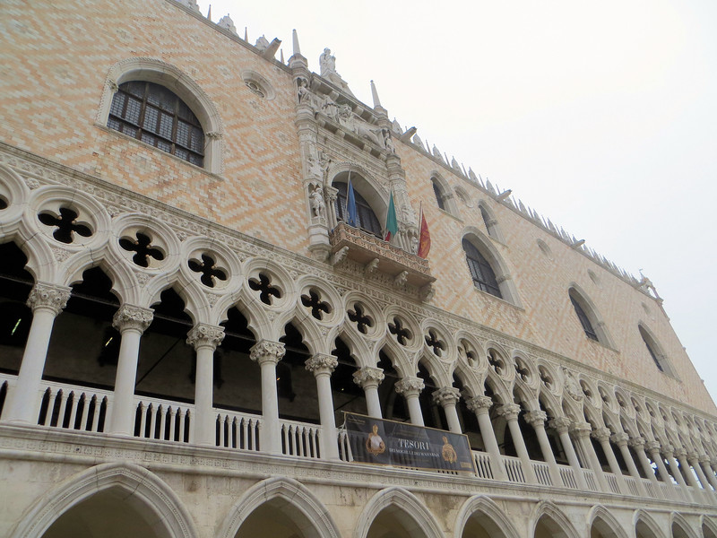 To the right of the Basilica is the Doge's Palace.  It really is that sort of pink color.  Its architectural style is known as Venetian Gothic.   The traditional Gothic arches are modified with Eastern influences.  This style appears elsewhere in the city, e.g. on the palazzos that line the Grand Canal.