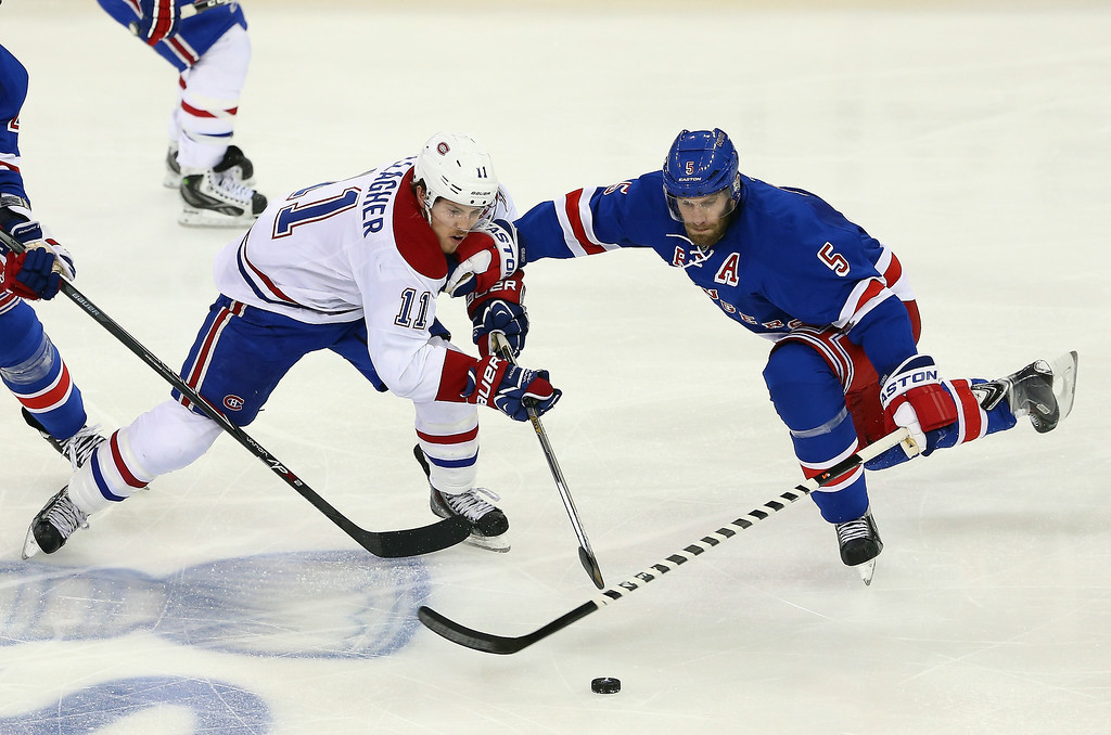 . Brendan Gallagher #11 of the Montreal Canadiens and Dan Girardi #5 of the New York Rangers battle for the puck during Game Six of the Eastern Conference Final in the 2014 NHL Stanley Cup Playoffs at Madison Square Garden on May 29, 2014 in New York City.  (Photo by Elsa/Getty Images)