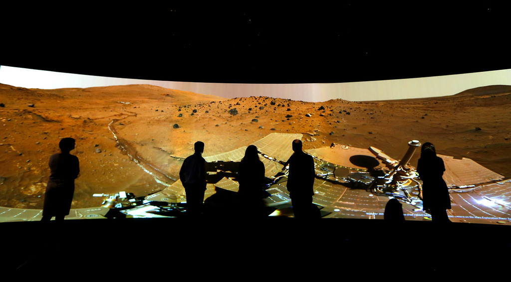 ". FILE - In this Wednesday, June 5, 2013 file photo, people look at the ""Mars Window,\"" a projection of images taken by NASA\'s Mars Curiosity Rover at the Visions of the Universe exhibition at The National Maritime Museum in Greenwich, London. (AP Photo/Kirsty Wigglesworth)"
