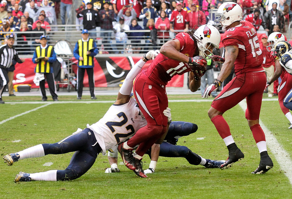 . Arizona Cardinals wide receiver Larry Fitzgerald (11) scores a touchdown as St. Louis Rams cornerback Trumaine Johnson (22) defends during the first half of an NFL football game, Sunday, Dec. 8, 2013, in Glendale, Ariz. (AP Photo/Rick Scuteri)