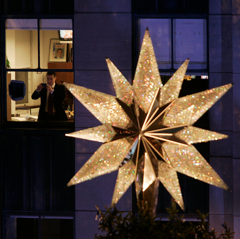 . An office worker takes a picture from the seventh floor of a building at Rockefeller Center before the 74th annual Rockefeller Christmas tree lighting ceremony, Wednesday, Nov. 29, 2006 in New York. A Swarovski star sitting atop the 88-foot tall tree was at eye level. (AP Photo/Julie Jacobson)