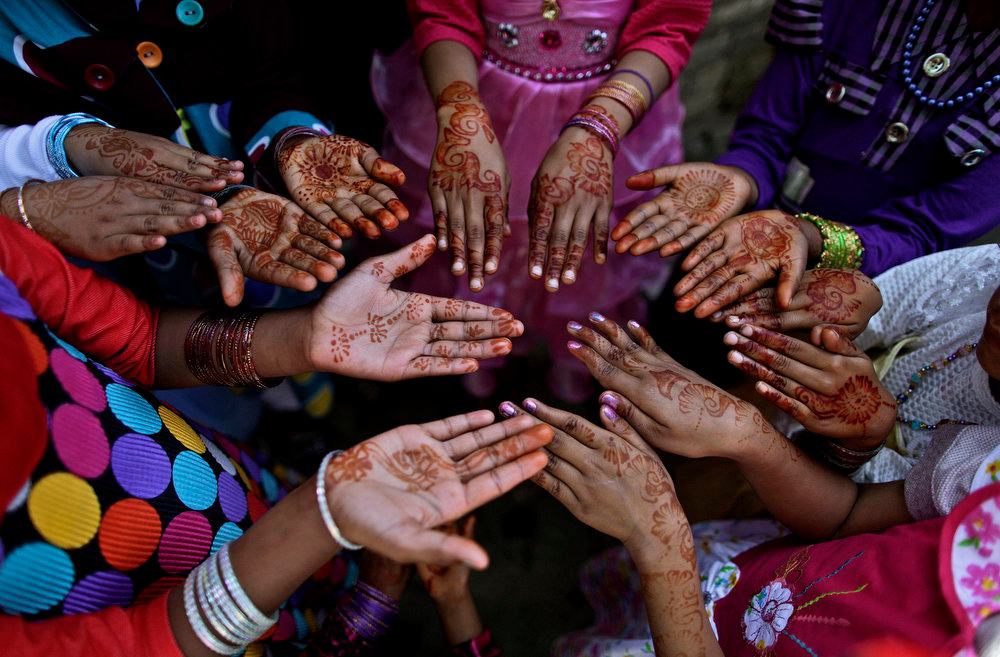 . Pakistani Christian girls, display their hands decorated with Bangles and painted with Henna paste as they celebrate Easter holiday following a mass at in a Christian neighborhood in Islamabad, Pakistan, Sunday, March 31, 2013. Pakistan\'s Christians, are celebrating Easter along with other Christian nations. (AP Photo/Muhammed Muheisen)