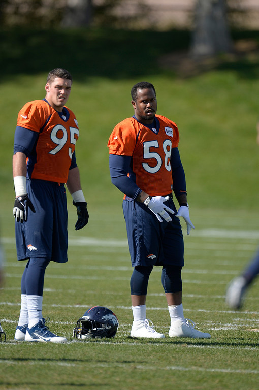 . Denver Broncos defensive end Derek Wolfe (95) and Denver Broncos outside linebacker Von Miller (58) look on during stretching before practice October 16, 2013 at Dove Valley. This is Von Millers first day back at practice with the team after serving his six game suspension. (Photo by John Leyba/The Denver Post)